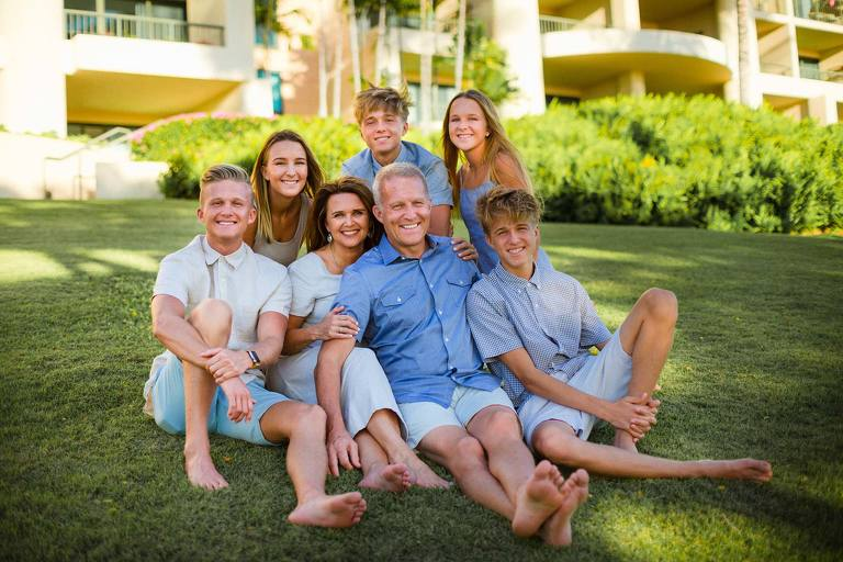 family sitting on the grass in hawaii